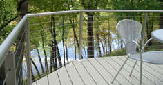 Residential stainless steel cable rail photo with light clay aluminum plank decking with a view of a lake by Versadeck Decking